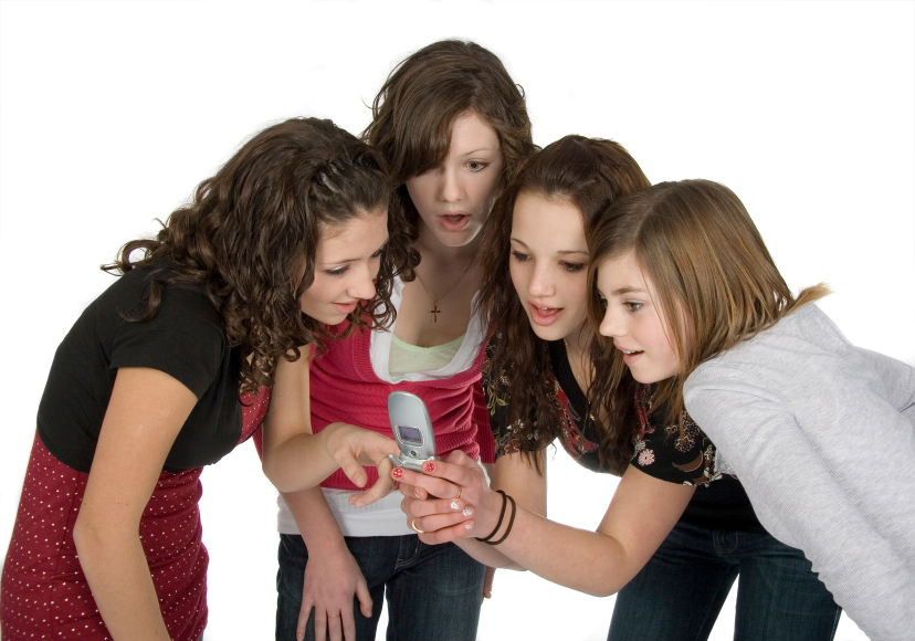 four teen girls looking at cell phone